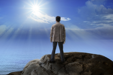 Photo for young man standing on rock mountain and looking to the sun for multipurpose - Royalty Free Image