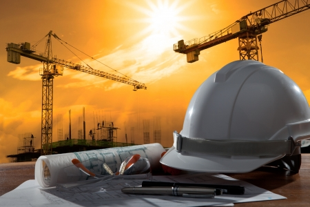 Photo pour file of safety helmet and architect pland on wood table with sunset scene and building construction - image libre de droit