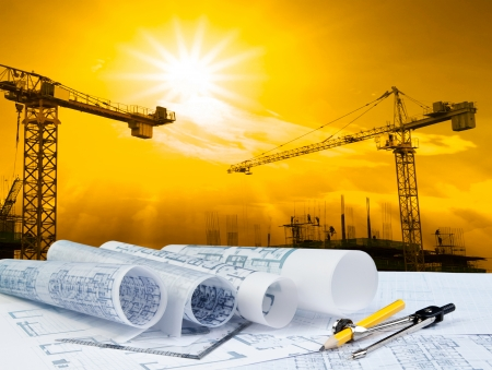 Foto de architect plan on working table with crane and building construction  - Imagen libre de derechos