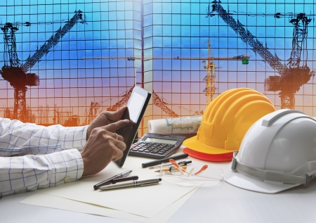Photo pour hand of architect working on table with tablet computer and working tool equipment against reflection of office building and crane construction use for civil engineering and construction industry business - image libre de droit
