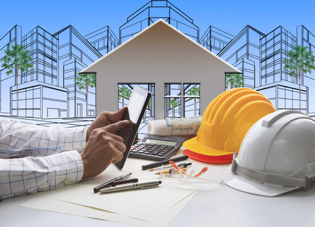 Photo pour hand of architect working on computer tablet  with construction industry and engineer working tool on top of table against home out line and sketching of modern building perspective - image libre de droit