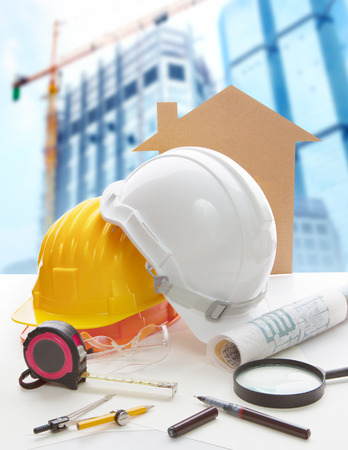Foto de safety helmet blue print plan and construction equipment on architect ,engineer working table with building construction crane background use for construction industry business and civil engineering  - Imagen libre de derechos