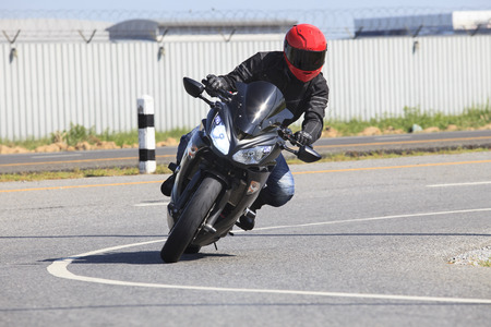 young man riding motorcycle in asphalt road curve use for male activities in holiday and traveling theme