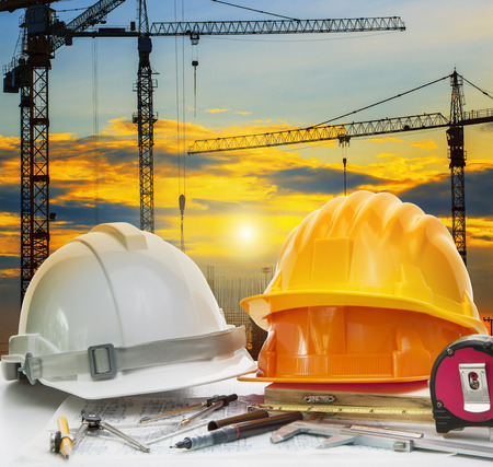 Photo pour civil engineer working table with safety helmet and writing instrument against beautiful dusky sky and crane construction site - image libre de droit