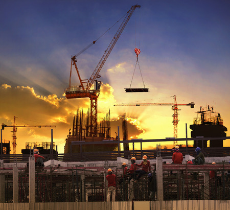 Photo pour worker working in high building construction site against beautiful dusky sky use for construction business and land ,real estate ,civil development - image libre de droit
