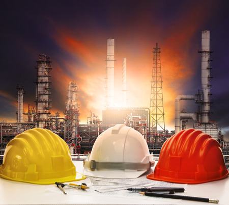 Foto de safety helmet and working sheet on engineer working table with oil refinery background - Imagen libre de derechos