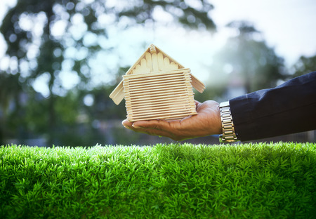 Photo pour hand of business man and wood house model on beautiful green grass field use for housing ,residental real estate  and land development - image libre de droit