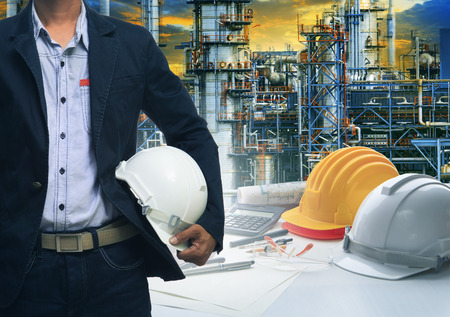 Photo pour engineering man standing with white safety helmet against  oil refinery in petrochemical industry - image libre de droit