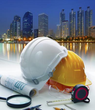 Foto de engineer working table with safety helmet and writing equipment against beautiful lighting of building in urban scene - Imagen libre de derechos