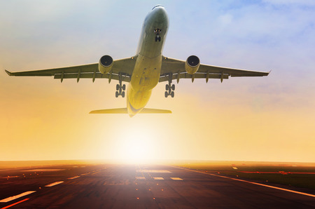 Photo pour passenger jet plane take off fron airport runway with beautiful light of sun rising behind - image libre de droit