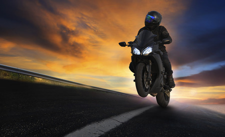 Foto de young man riding motorcycle on asphalt highways road with professional extreme biking skill use for sport racing and people vacation activities - Imagen libre de derechos