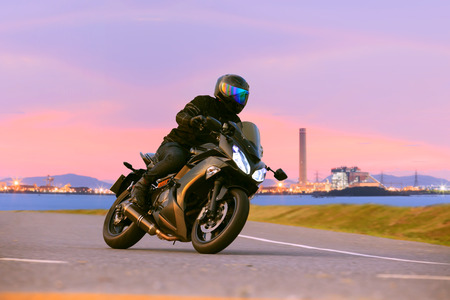 Foto de young man riding sport touring motorcycle on asphalt highways against beautiful lighting of urban industry scene use as modern people lifestyle and holiday activities - Imagen libre de derechos