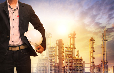 Photo pour engineering man with white safety helmet standing in front of oil refinery building structure in heavy petrochemical industry - image libre de droit