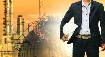 Foto de engineering man and safety helmet standing against oil refinery plant in heavy petrochemical industrial estate - Imagen libre de derechos