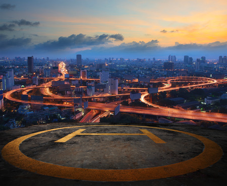 Photo for helicopter pad on top building roof against beautiful express way and land transportation in dusky sky city scape - Royalty Free Image
