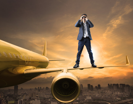 Photo for business man and binoculars lens standing on plane wing spying acting use for commercial competition and top secret strategy - Royalty Free Image