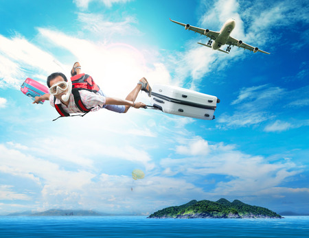 Photo pour young man flying on blue sky wearing snorkeling mask and holding luggage use for people traveling by plane to destination sea island and summer vacation holiday theme - image libre de droit