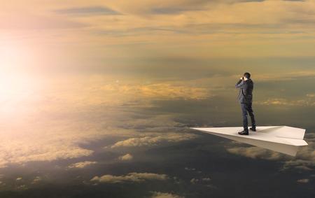Foto de business man standing and spying binocular on papet plane against sun rising over cloud scape - Imagen libre de derechos