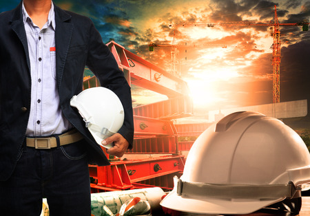 Photo for engineer man with white safety helmet standing against working table and building construction scene - Royalty Free Image
