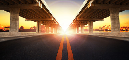 Foto per sun rising behind perspective on bridge ram construction and asphalt raod perspective to ship port background use for infra land and vessel transportation - Immagine Royalty Free