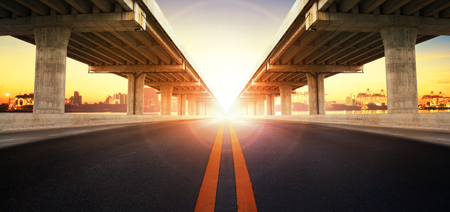 Foto de sun rising behind perspective on bridge ram construction and asphalt raod perspective to ship port background use for infra land and vessel transportation - Imagen libre de derechos