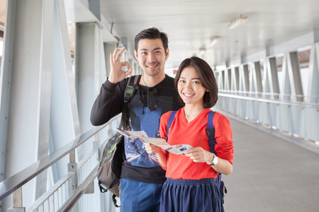 Foto de younger asian traveling man and woman standing with toothy smiling face sigh all right by okay hand sue for modern people backpacker traveling lifestyle - Imagen libre de derechos