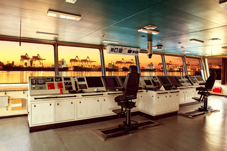 Foto per wheelhouse control board of modern industry ship approaching to harbor at night - Immagine Royalty Free