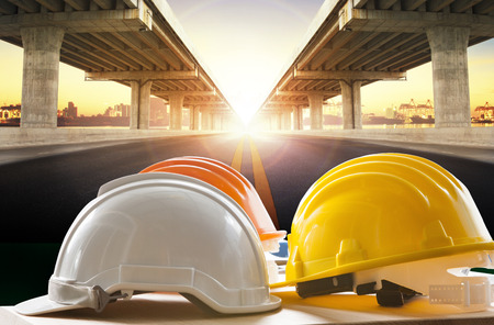 Photo for safety helmet on civil engineering working table against bridge construction in urban scene - Royalty Free Image