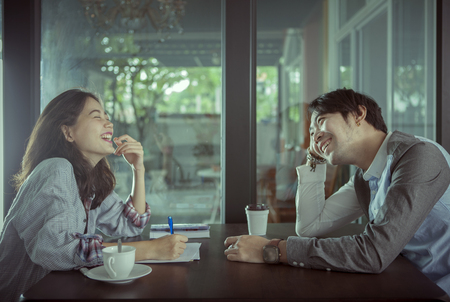 Photo for couples of younger asian man and woman relaxing with hot coffee drink in coffee shop happiness feeling - Royalty Free Image