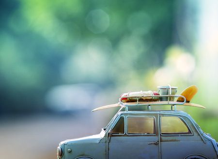 Foto de old classic retro car with surf board and beach  tool on roof against beautiful blur background for vacation traveling theme - Imagen libre de derechos