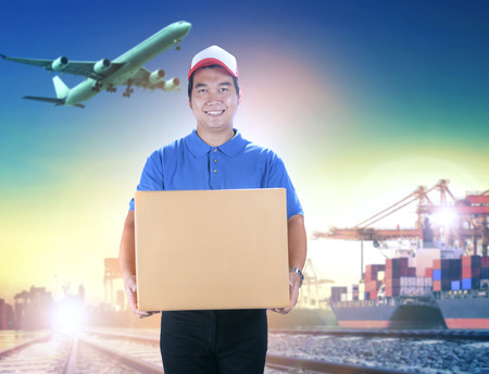 Photo for delivery man holding card box toothy smiling face against shipping port and cargo plane flying background - Royalty Free Image