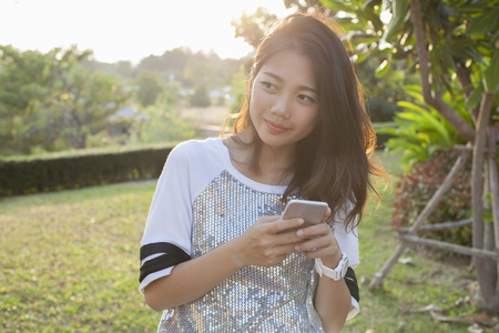 Photo pour asian younger woman with smartphone in hand happiness thinking ,relaxing outdoor - image libre de droit