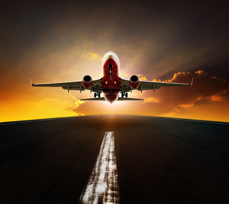 Foto de passenger plane take off from airport runway agasint beautiful sun rising sky - Imagen libre de derechos