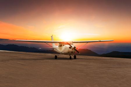Photo pour old propeller plane taxi on airport runway against beautiful sun set sky - image libre de droit