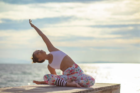 Photo for younger woman playing yoga pose on sea pier  - Royalty Free Image