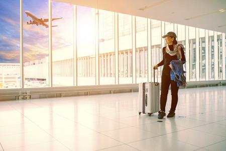Foto de single woman and traveling luggage standing in airport terminal building - Imagen libre de derechos
