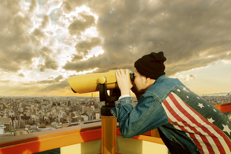 Photo for hipster man wearing american flag jeans jacket looking through binocular lens against urban building - Royalty Free Image