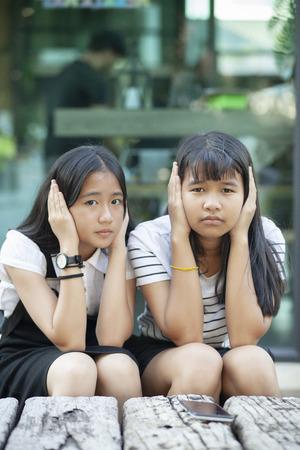 Foto de two asian teenager using hand close her ear for not listening any sound - Imagen libre de derechos