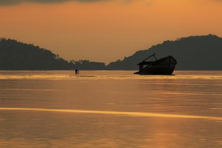 Foto de photographer taking a photo of wreck boat on shallow sea beach against beautiful sun rising sky - Imagen libre de derechos