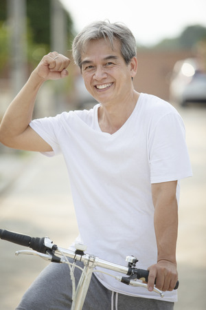 Foto de middle age asian man toothy smiling face happiness emotion exercise by riding bicycle in home village street - Imagen libre de derechos