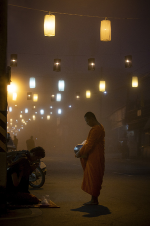 Photo for maehongsorn thailand - jan22,2017 : thai buddhist monk receiving food from people on foggy street in maehongsorn northern of thailand - Royalty Free Image