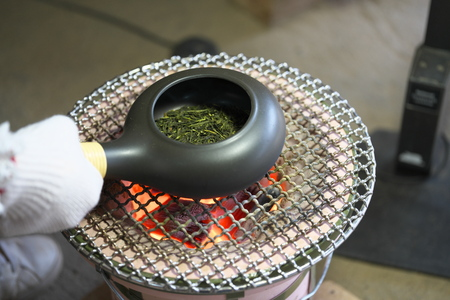 Foto de Chiba, Japan-February 19, 2019: Roasting green tea with an earthenware baking pan on Earthen charcoal brazier. Roasted green tea is called Hojicha in Japanese. - Imagen libre de derechos