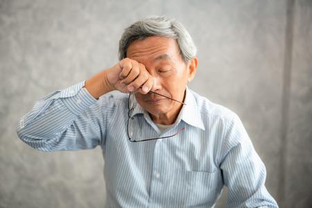 Foto de Senior man is holding eyeglasses and  rubbing his tired eyes while reading e-book in tablet. - Imagen libre de derechos