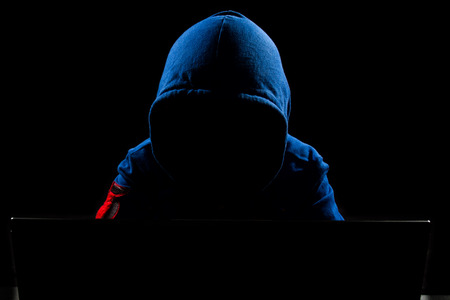 Foto de Faceless hacker with laptop in black isolated background. - Imagen libre de derechos