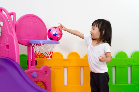 Photo pour Asian Chinese little girl playing basketball at indoor colourful playground - image libre de droit
