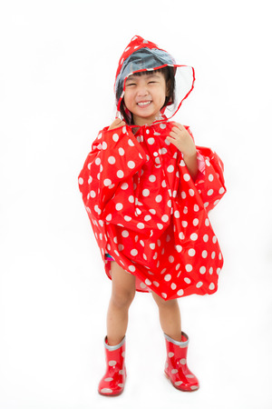 Chinese Little Girl Wearing raincoat and Boots in plain white isolated background.