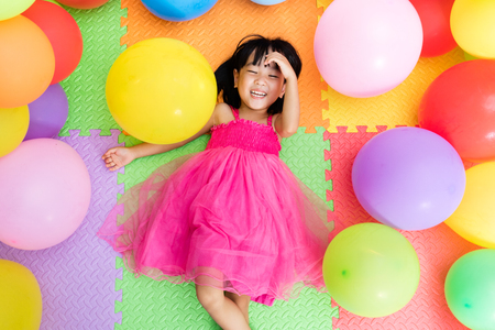 Photo pour Asian Little Chinese Girl Lying on the Floor amongst Colorful Balloons in Indoor Playground - image libre de droit