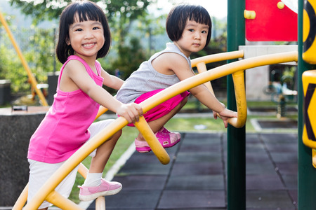 Photo pour Asian Chinese little girl climbing at outdoor playground. - image libre de droit