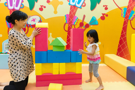 Photo pour Asian Chinese Mom and Daugther Playing Giant Blocks At Indoor Playground. - image libre de droit