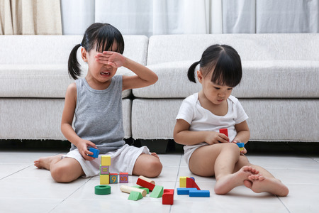 Photo pour Asian Chinese little sisters struggle for blocks on the floor in the living room at home. - image libre de droit